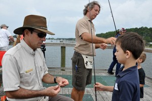 Volunteers put bait on the lines while kids test their new fishing skills at the FWC Kids' Fishing Clinic in Panacea. Florida Fish and Wildlife Conservation Commission Kids' Fishing Clinics are statewide events that introduce kids to saltwater fishing and ethical angling. April 21, 2012 Amanda Nalley. Photo: MyFWC Media